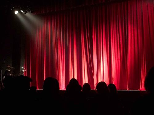 Imagen. Telón rojo de teatro iluminado por dos focos.